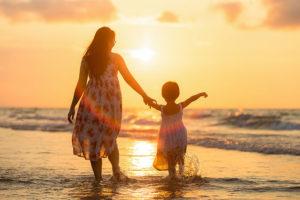 Mothr and daughter walking on beach